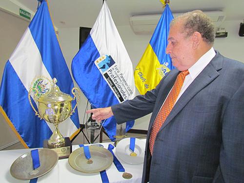 Presidente de APAC muestra otros premios ganados por su academia.